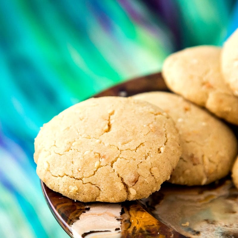 Photo of several baked ghoriba bahla cookies. In the picture, the Moroccan shortbread has obvious bits of toasted sesame seeds and ground, fried almonds mixed in.