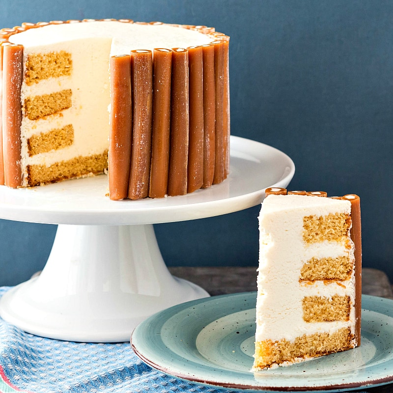 Caramel cake with white icing and Cow Tales caramels on a pedestal with a slice cut out and on a plate.