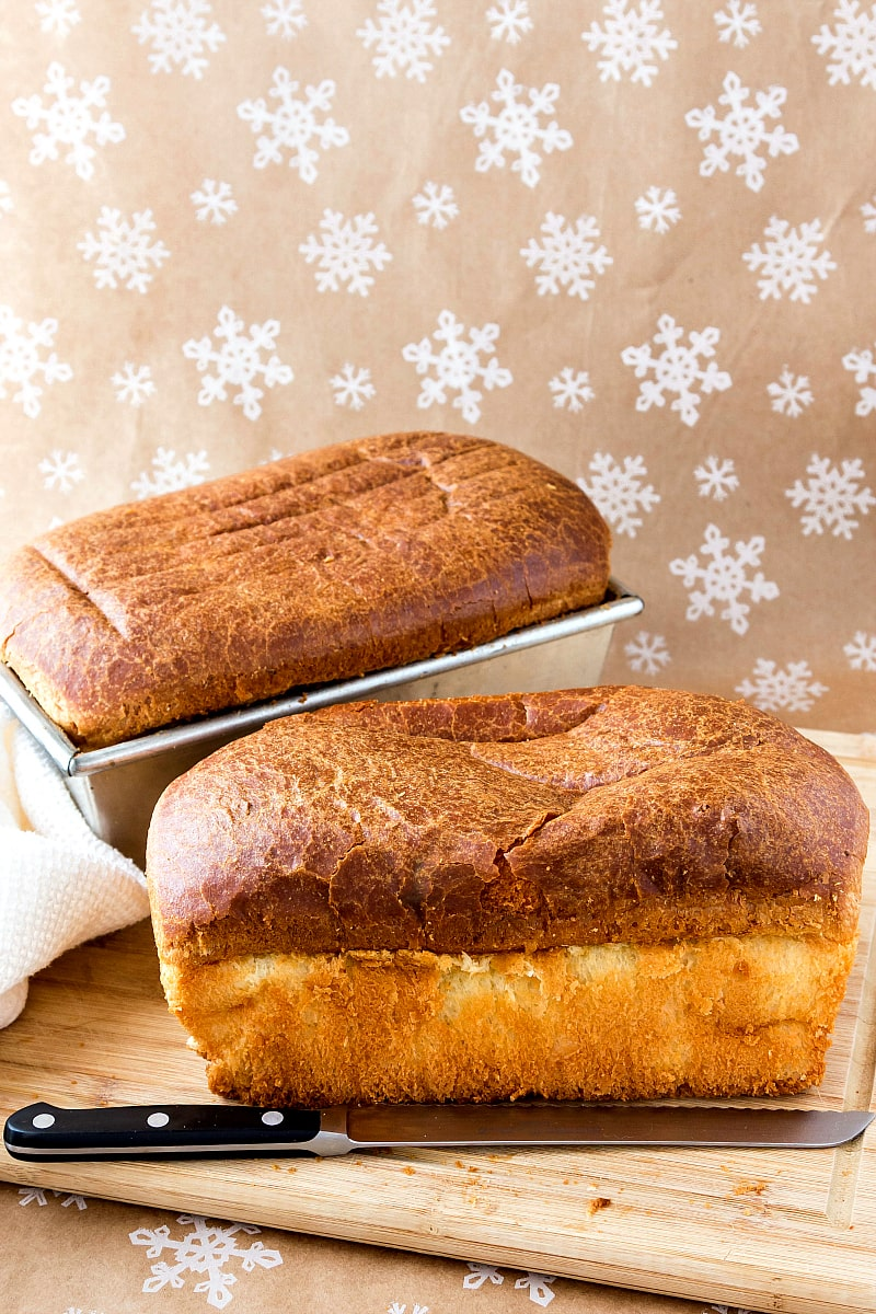 2 loaves of bread, one on a cutting board with a knife and one in the pan