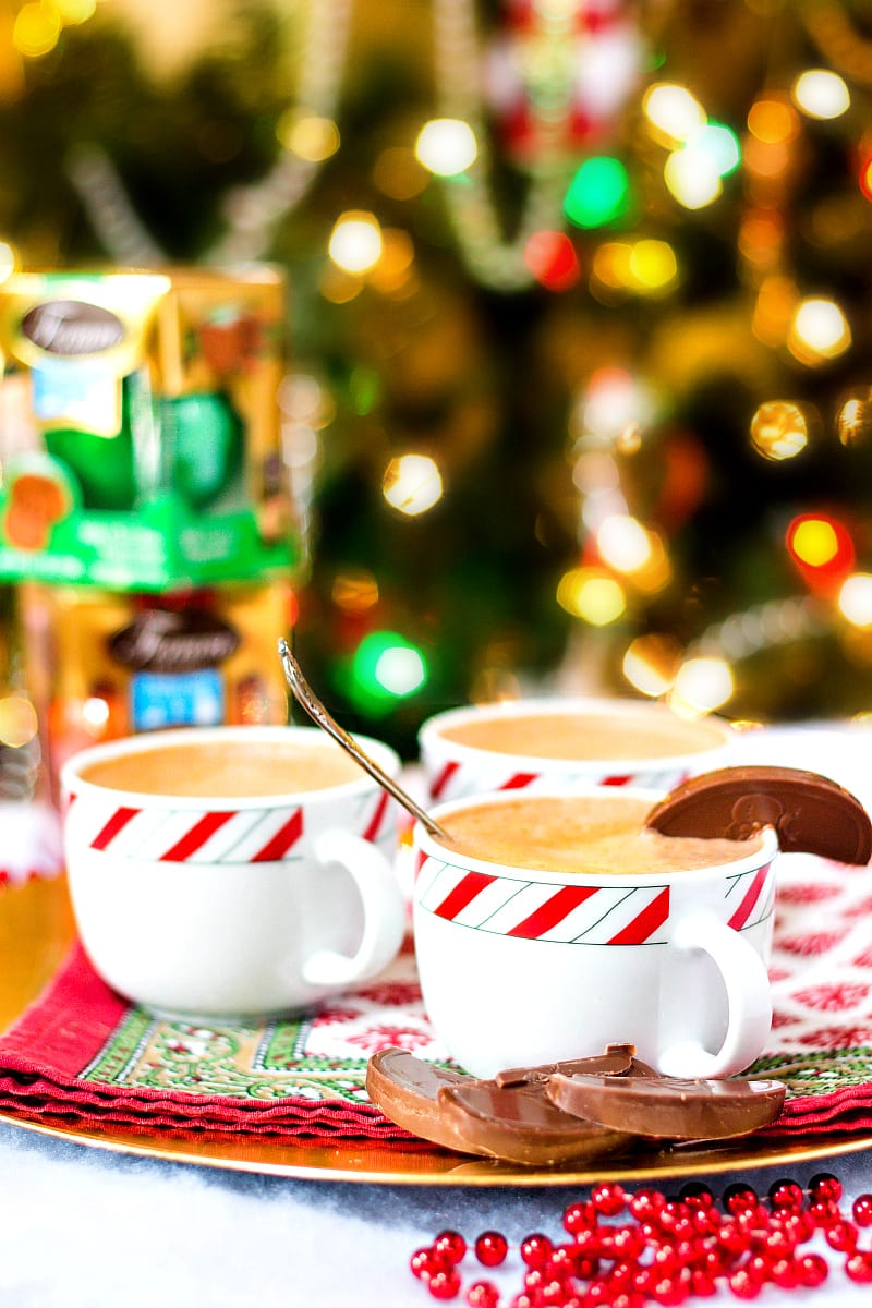 3 holiday mugs of hot chocolate on a platter with a Christmas tree in the background.