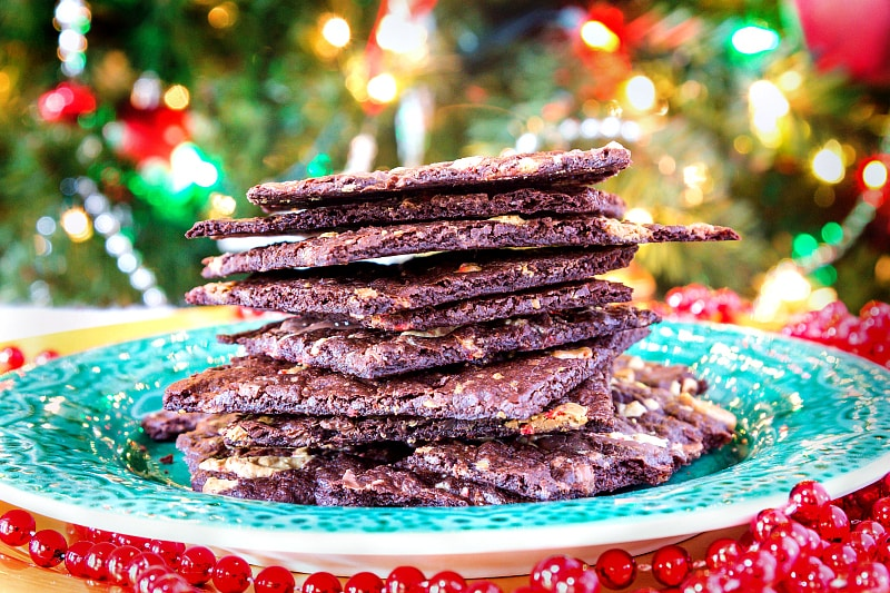 A pile of thin and crisp brownie bark from a peppermint brownie brittle recipe stacked on a green plate with a Christmas tree in the background.