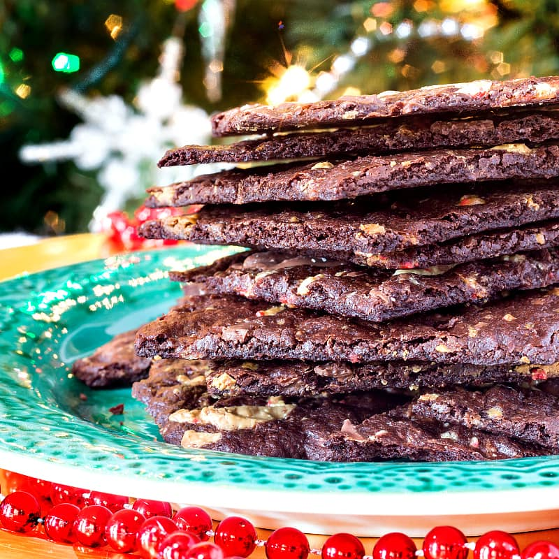 A stack of peppermint brownie brittle shot from the side on a green plate with a Christmas tree in the background.