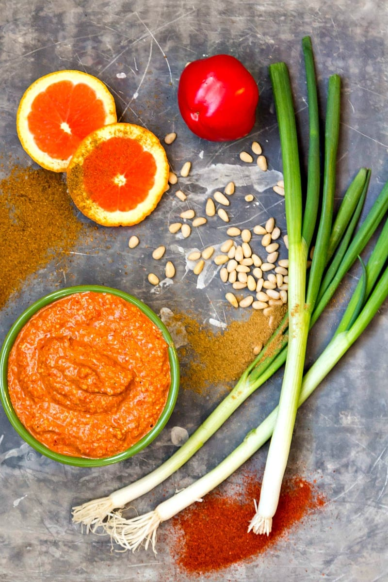 A bowl of blood orange muhammara, slices of blood orange, a red pepper, green onions, pine nuts and spices on a tray.