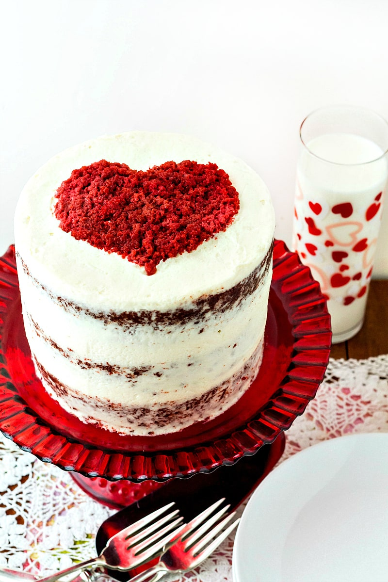 3/4 view of tall stacked red velvet cake frosted in white with a red heart on top