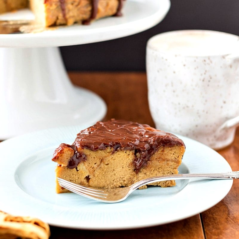 A plate with a triangular slice of chocolate glazed bread pudding with a fork.