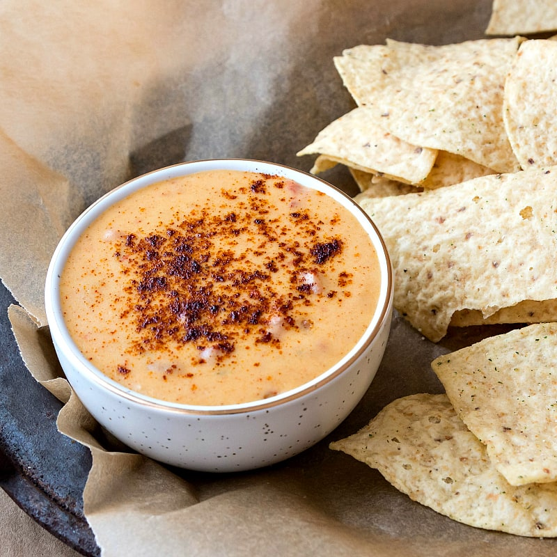 A bowl of spicy queso with tortilla chips.