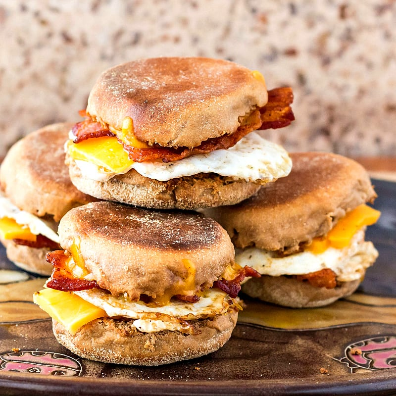 a stack of fried egg, bacon and cheese sandwiches made on homemade English muffins