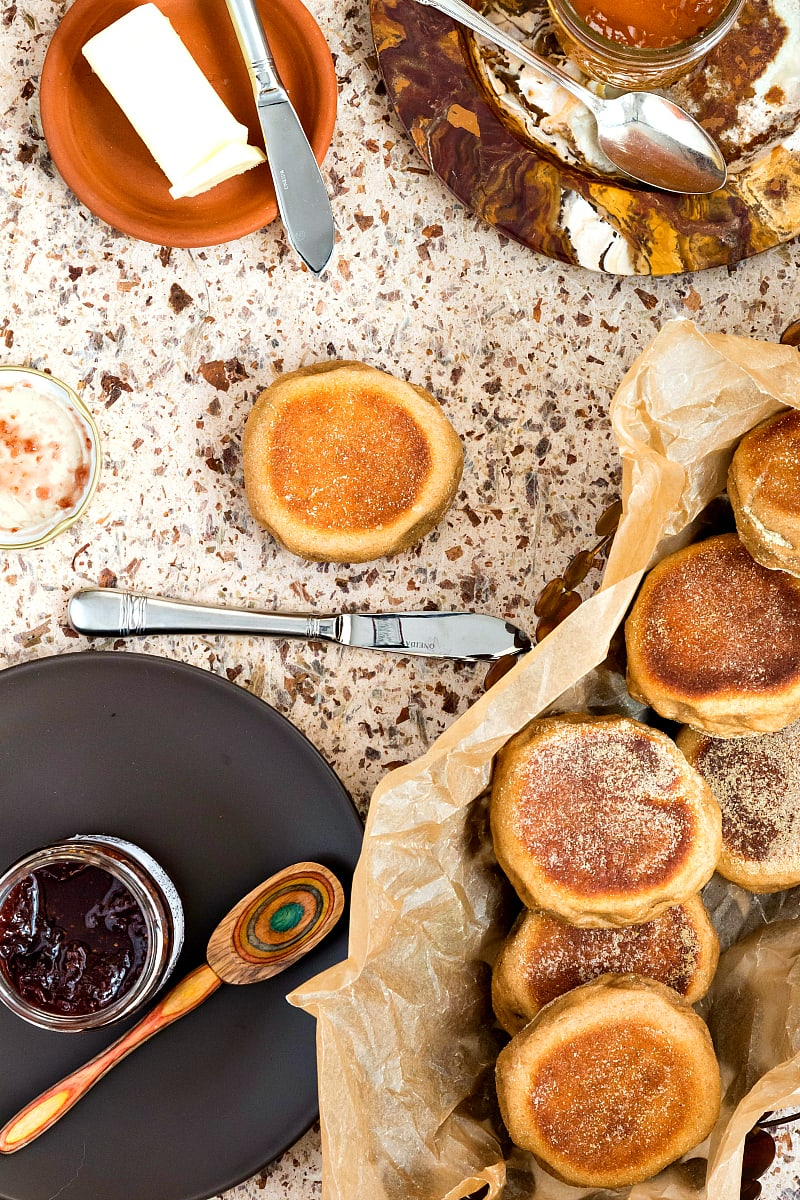 Overhead shot of English muffins in a basket, jam, and a butter knife.