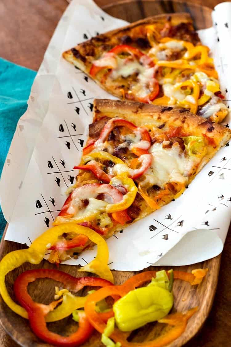 2 slices of bacon and pickled pepper pizza on paper.