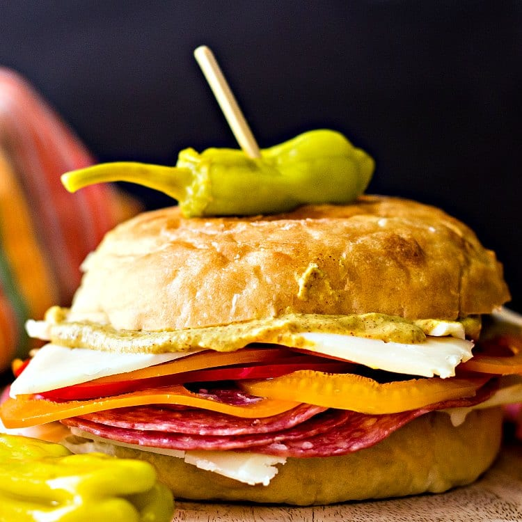 a sandwich made on a potato roll with cold cuts, sliced peppers, cheese, and mustard