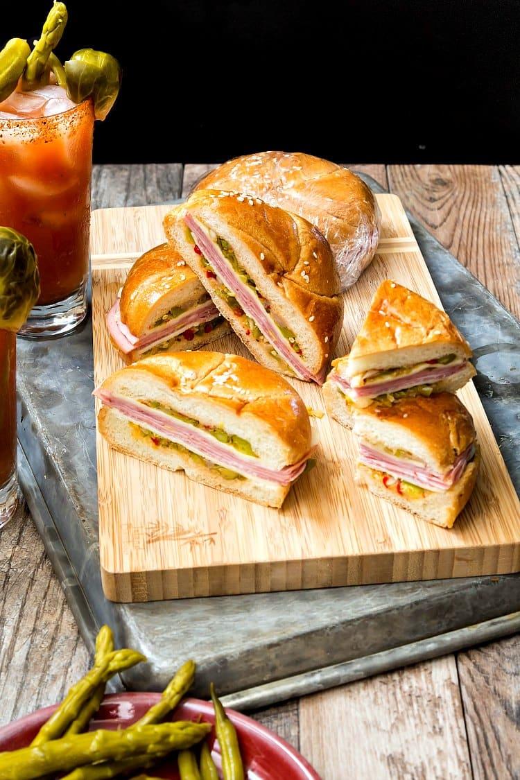 Several cut North Carolina Muffuletta sandwiches on a wooden board for serving.