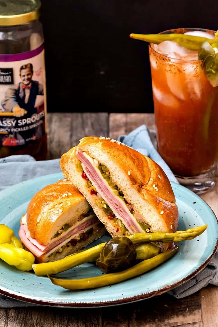 The North Carolina Muffaletta sandwich  sliced in half on a blue plate. A bloody mary in a clear glass is next to it.