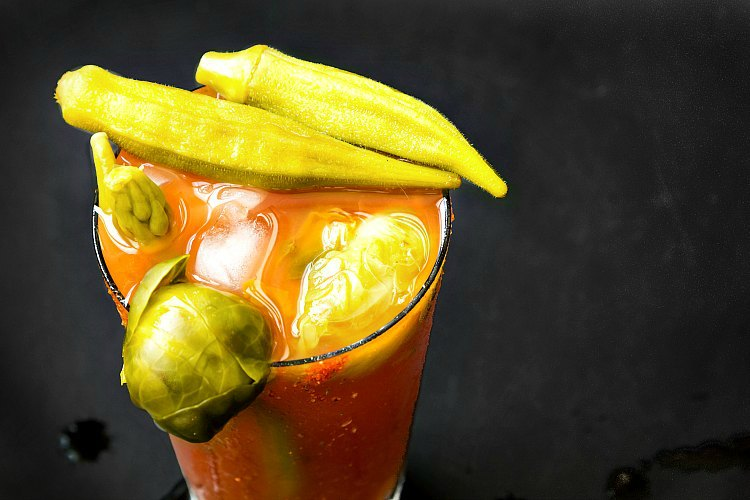 Pickled okra and brussels sprouts garnishing a clear glass full of bloody mary.