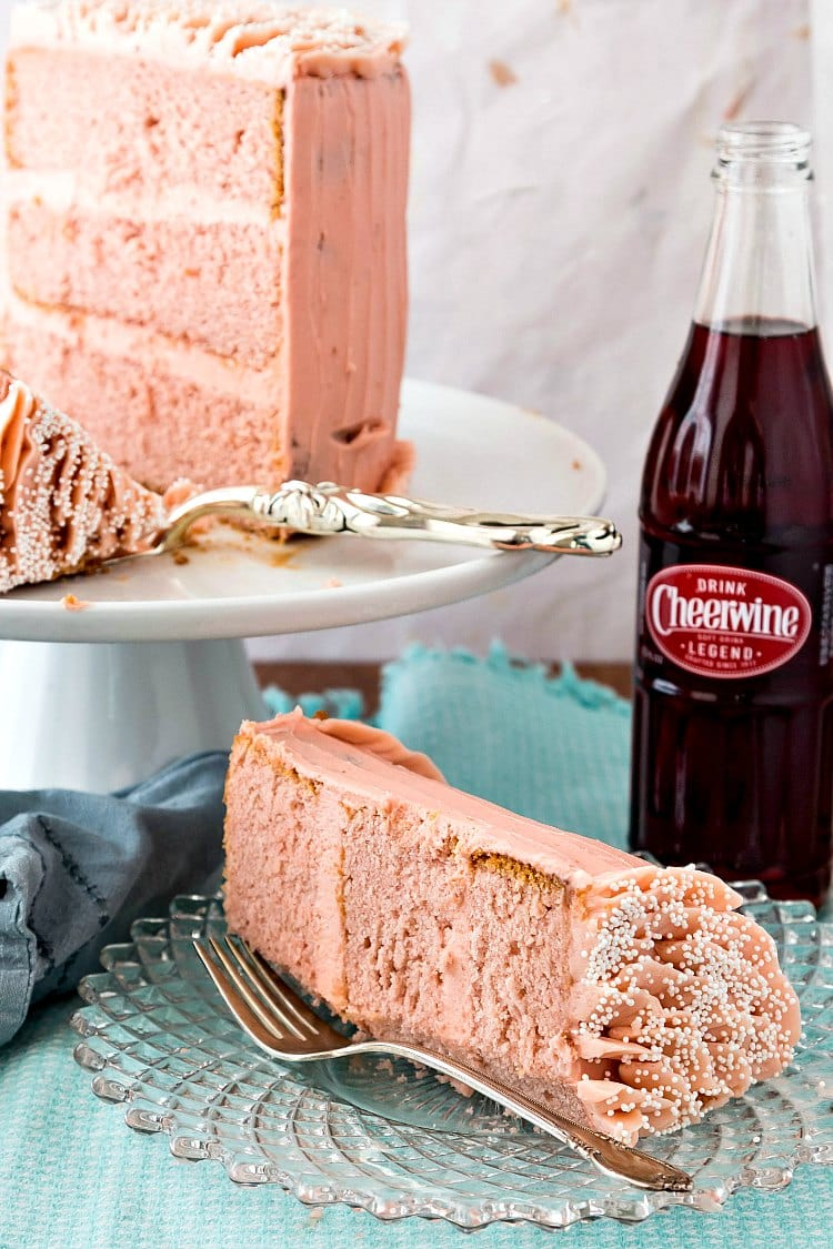 A slice of 3-layer Cheerwine cake with pink frosting with a bottle of Cheerwine and the rest of the cake on a platter.