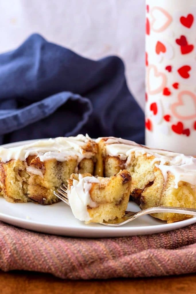 Cut and iced cinnamon roll on a white plate with a fork and a glass of milk in the background.