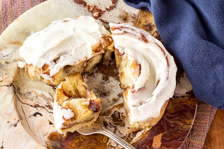 A cinnamon roll on a plate cut into pieces with a fork so you can see all the cinnamon roll filling inside.
