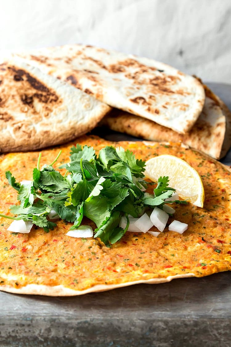 Tortillas spread with vegan hummus, with cilantro and onions on top.