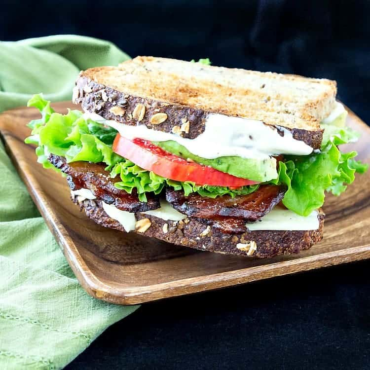 A BLT on toasted multigrain bread on a wooden plate.