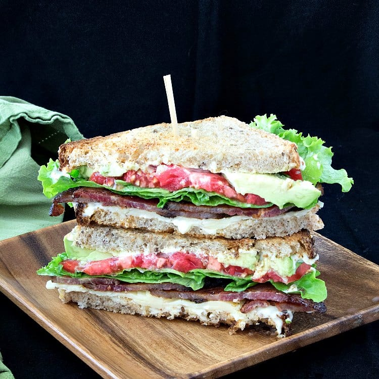 A sandwich with cheddar, bacon, lettuce, tomato, and avocado sliced in half diagonally and stacked on top of each other on a wooden plate.
