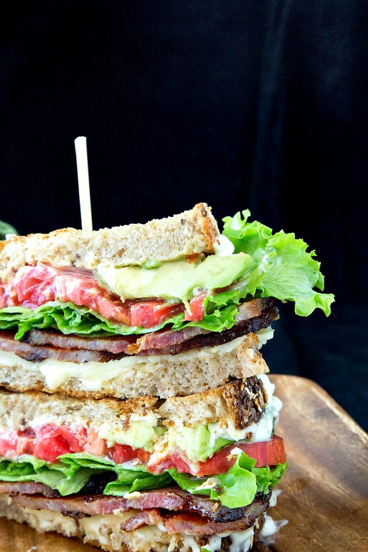A blt sandwich cut and stacked on a wooden plate.
