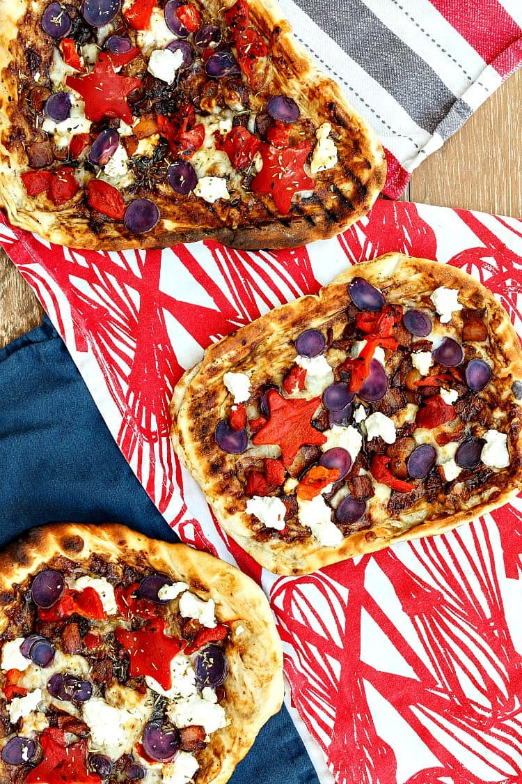 Two patriotic pizzas on red white and blue tea towels.