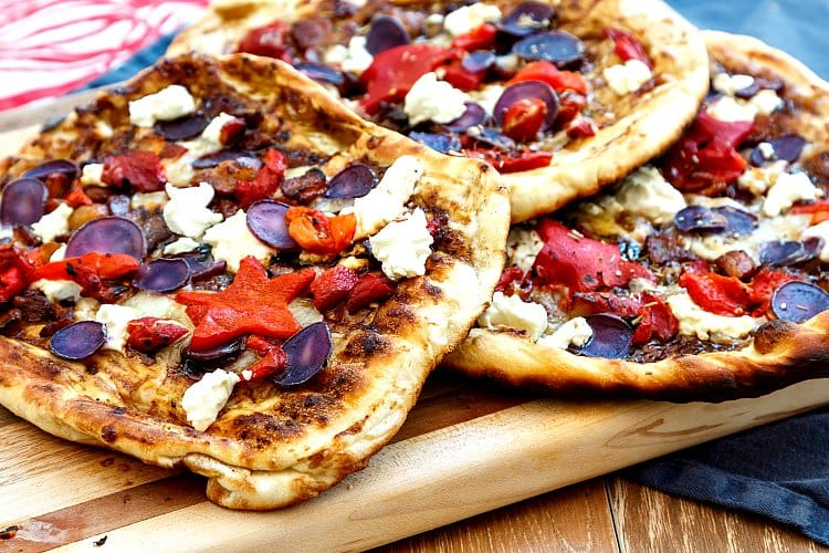 3 grilled pizzas with goat cheese, purple potatoes, and roasted red peppers on a wooden board.