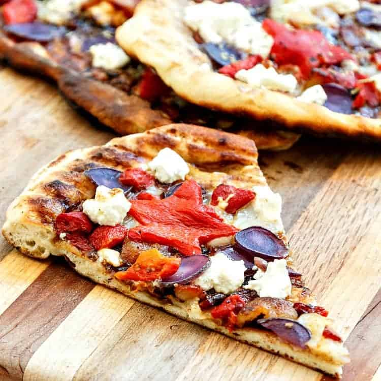 One slice of grilled pizza on a wooden table.