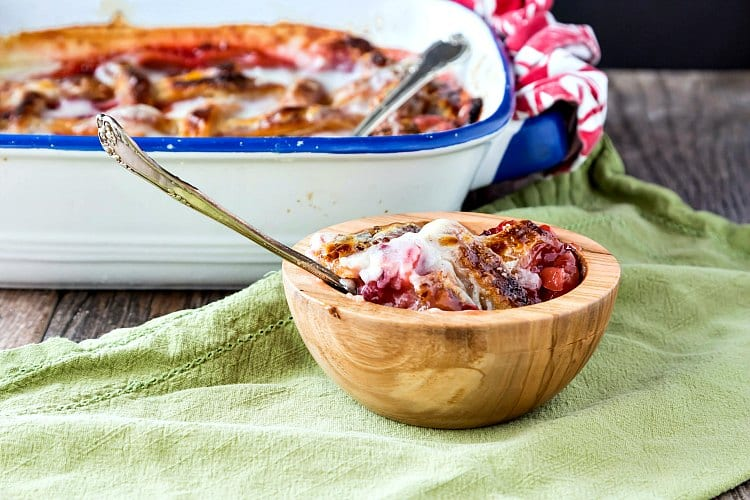 A bowl of cobbler and the baking dish of cobbler in the background.