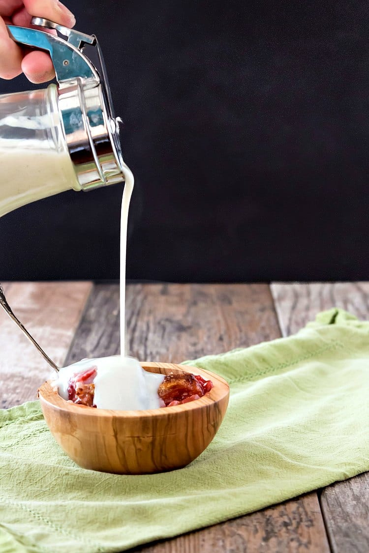 A pour shot of milk dip pouring over a wooden bowl of sonker.