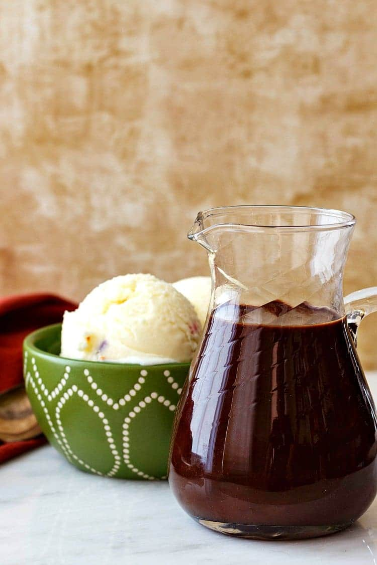 A green bowl of vanilla ice cream and a pitcher of easy fudge sauce.