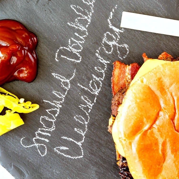 """An overhead shot of a burger and condiments on a piece of slate with """"smashed double cheeseburger"""" written in chalk on the slate."""