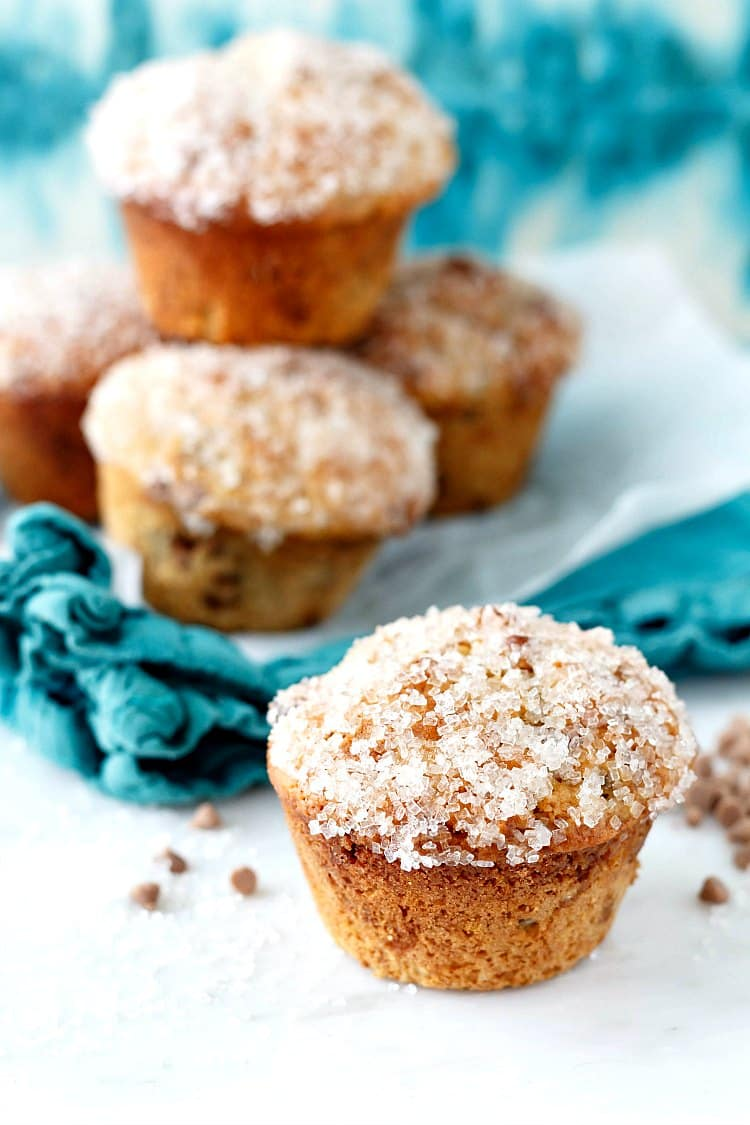A stack of cinnamon raisin muffins with sparkly sugar on their tops.