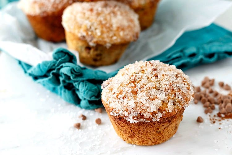 Cinnamon raisin muffins with sparkly sugar on their tops.