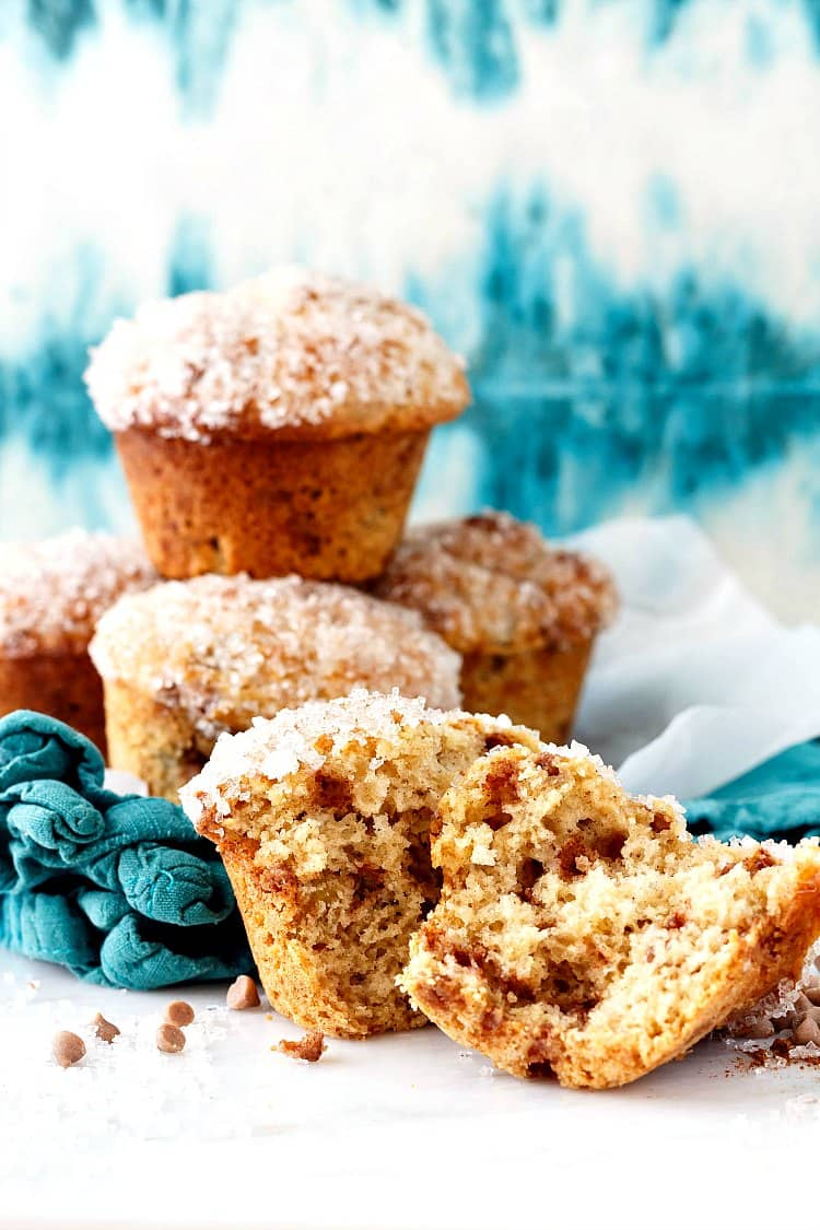 A pile of sugar-topped muffins. One in the foreground is split open to show the open crumb and cinnamon chips.