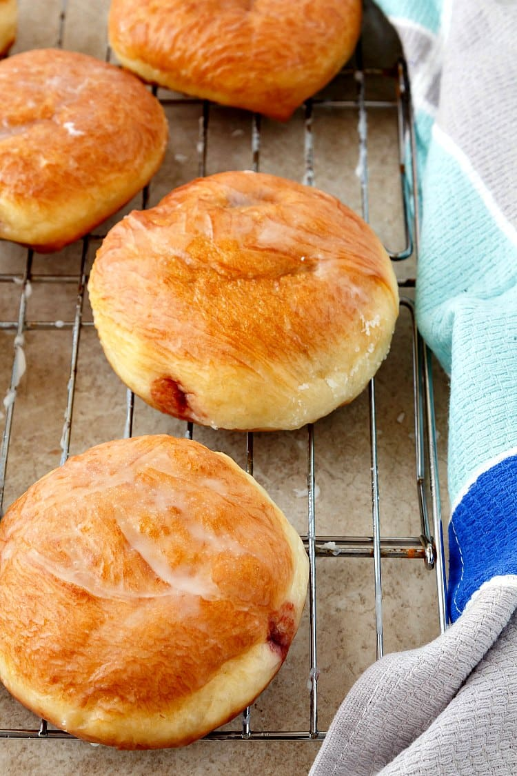 Raspberry filled doughnuts with a thin coating of glaze drying on a cooling rack.