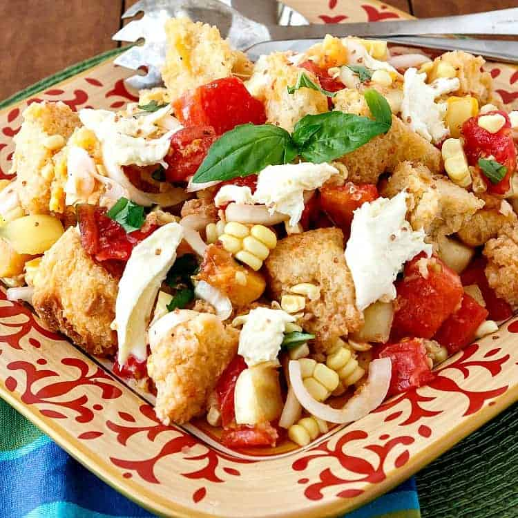 A square platter heaped with tomatoes, peaches, corn, basil, mozzarella cheese, and cubed bread.