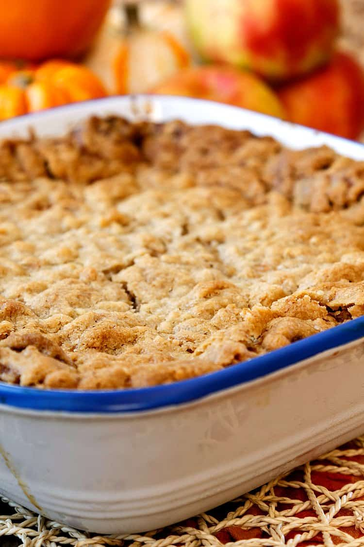 A square baking dish of streusel topped sweet breakfast casserole with apples in the background.