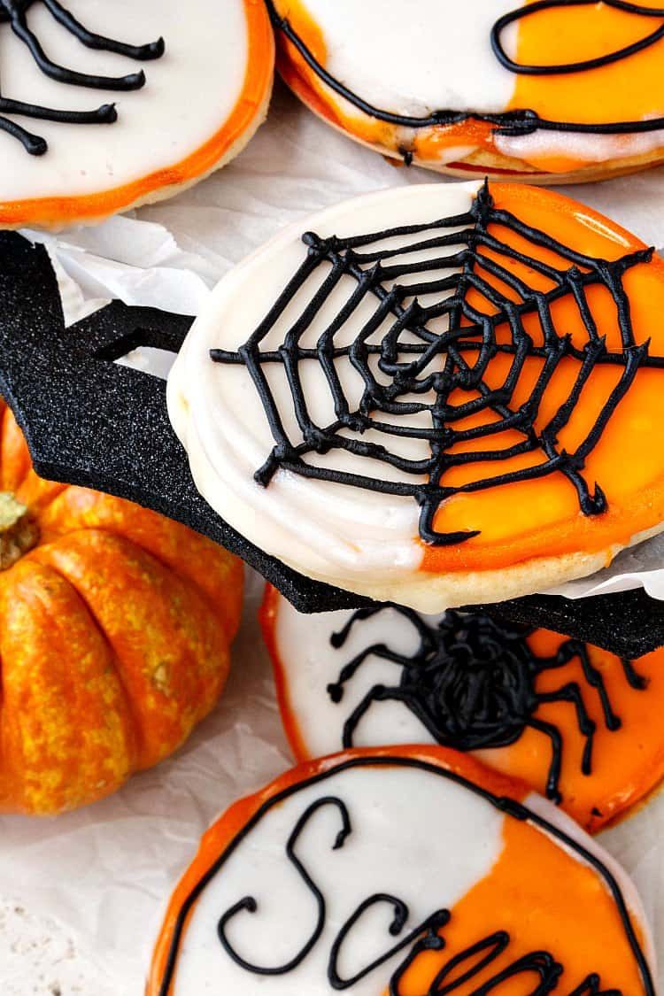 Close up of a black and white cookie with a spider web decoration for Halloween.