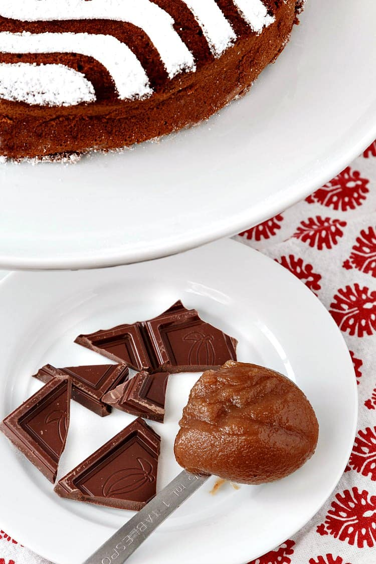 A whole chestnut chocolate torte next to a plate with pieces of chocolate and a spoonful of chestnut puree.