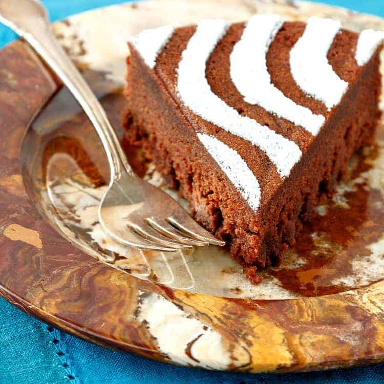 Slice of chocolate chestnut torte on a marbled plate with a silver fork ready for serving. The top is decorated with a design in powdered sugar.