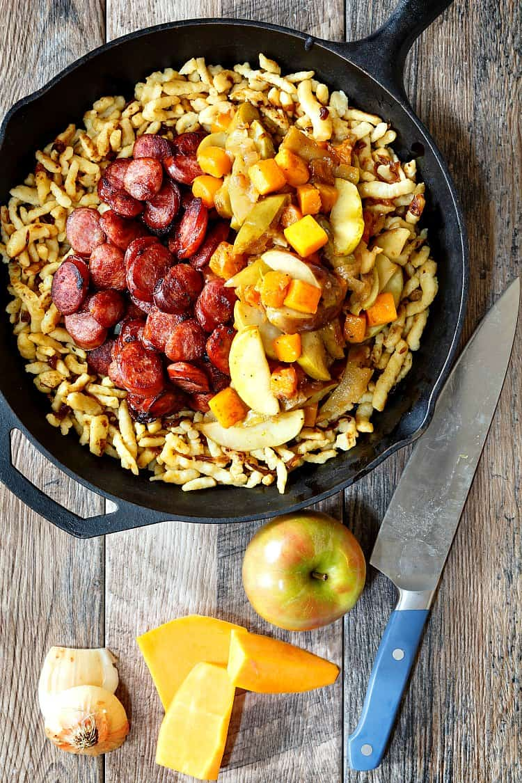 Polish sausage with apples, onions and butternut squash over spaetzle in a cast iron skillet.