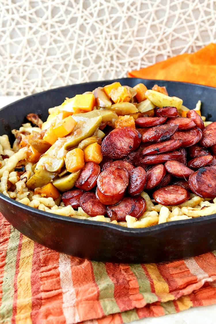 Polish sausage with apples onions and butternut squash over spaetzle in a cast iron pan.