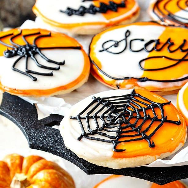 """A tray of orange and white iced cookies with spider decorations. Text on one of them reads """"Scary""""."""