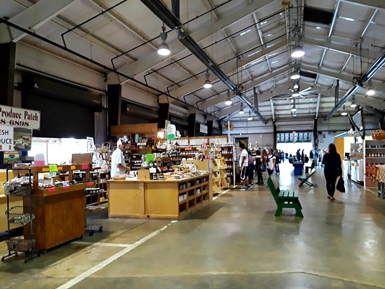 State farmers market in Raleigh, NC showing wide view of different vendors in a large hall with high ceilings and concrete floors.