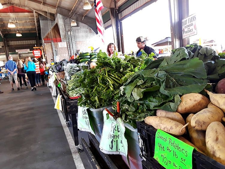 View of overflowing collards, sweet potatoes and other produce at state farmers market in Raleigh NC.
