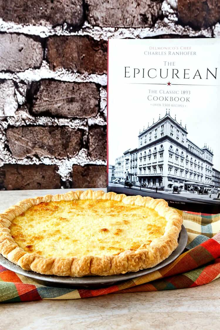 """A whole coconut pie in a metal pie pan next to book titled: """"Delmonico's Chef Charles Ranhofer, The Epicurean, The classic 1893 cookbook""""."""