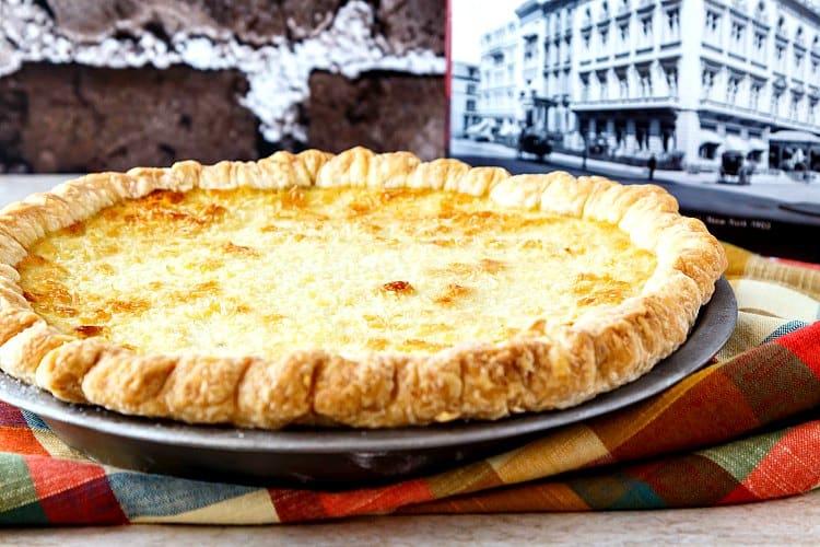 A whole coconut custard pie in a pie plate next to The Epicurean cookbook.