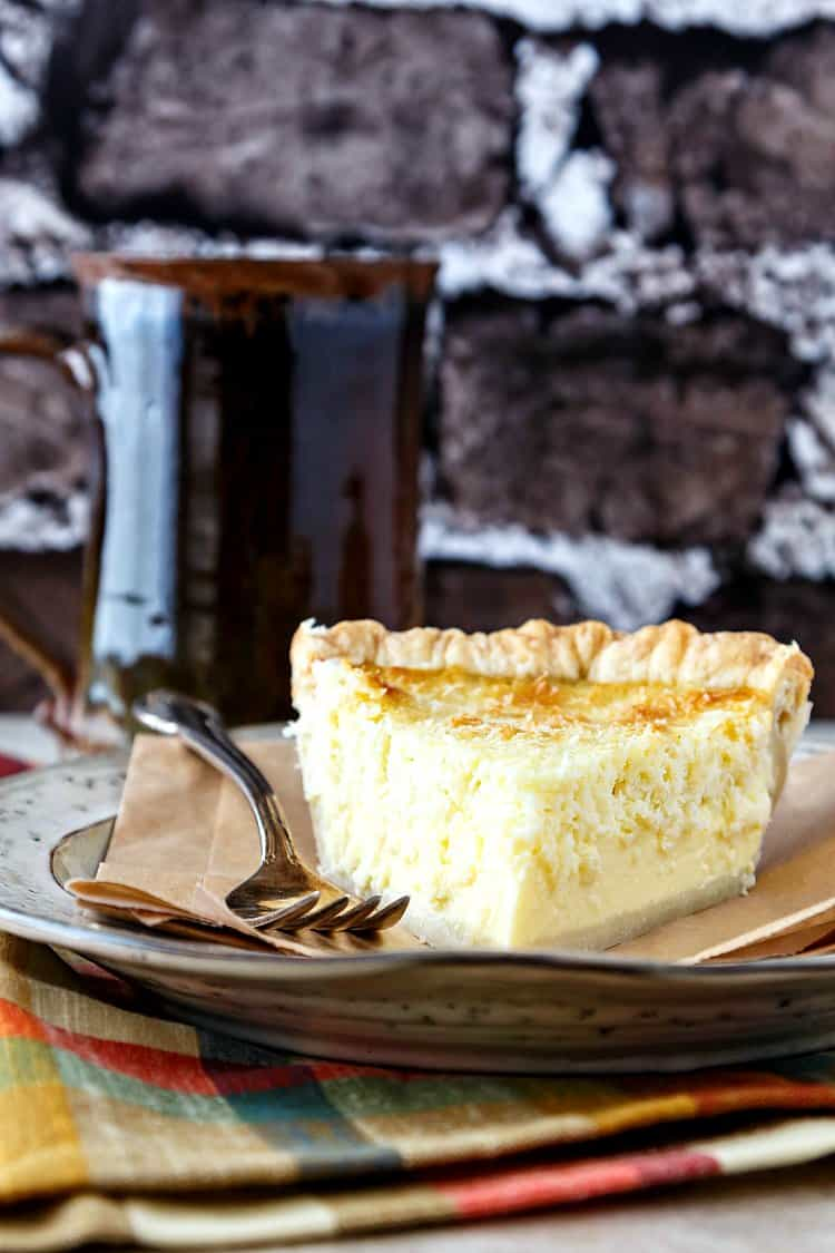 A slice of coconut pie with a fork on a beige plate.