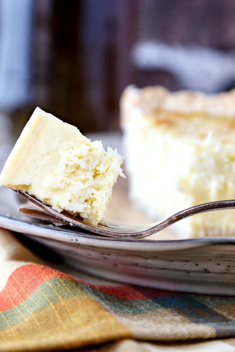 A close up of a bite of traditional coconut custard pie on a fork.