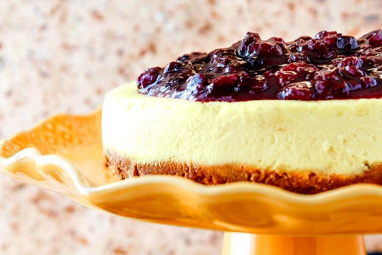 Close up view of the side of a cheesecake with fruit topping, sitting on an orange fluted cake stand.